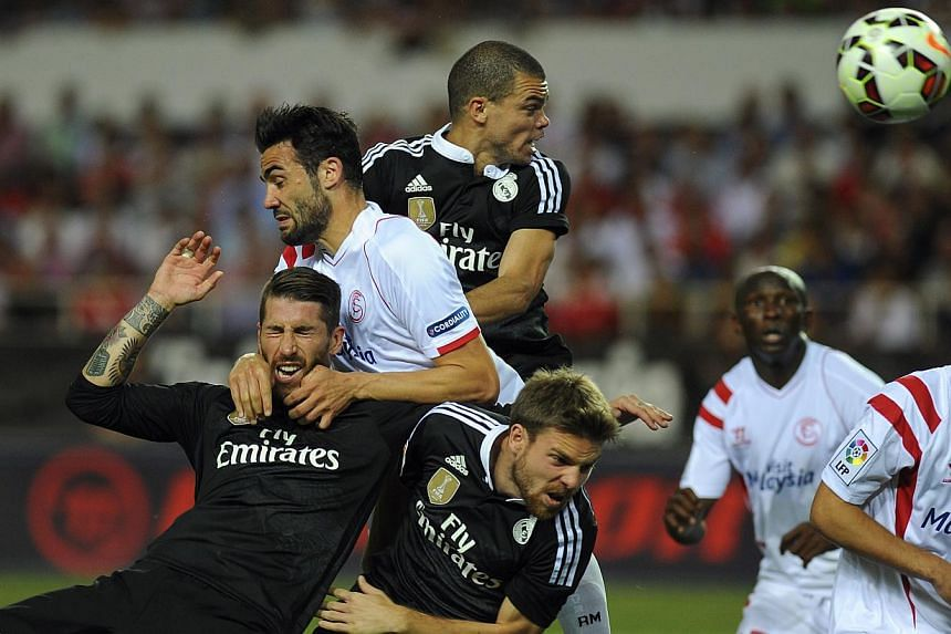 Real Madrid's defender Sergio Ramos (left), Portuguese defender Pepe (top right) and midfielder Asier Illarramendi (second left) vie with Sevilla's midfielder Vicente Iborra (top left) and midfielder Denis Suarez (right) during the Spanish league foo