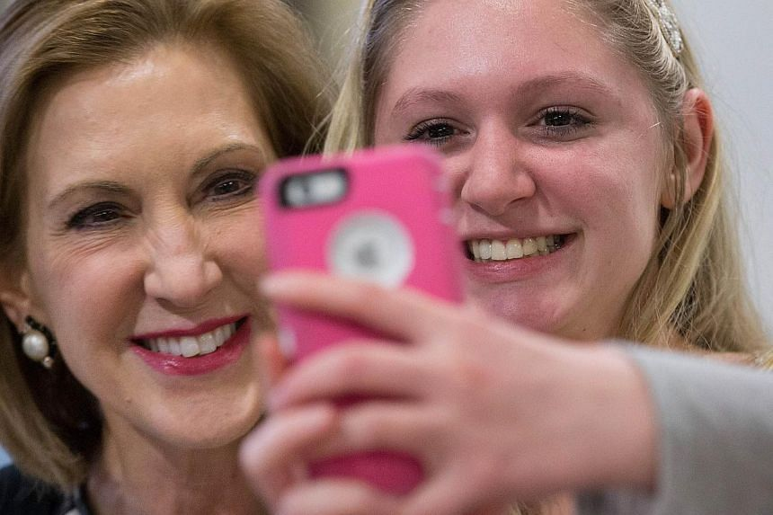 Mrs Carly Fiorina (left) posing for a selfie with a supporter at a Republican event at a high school in Iowa last month. Her mixed record at HP is under scrutiny ahead of her expected presidential bid today.