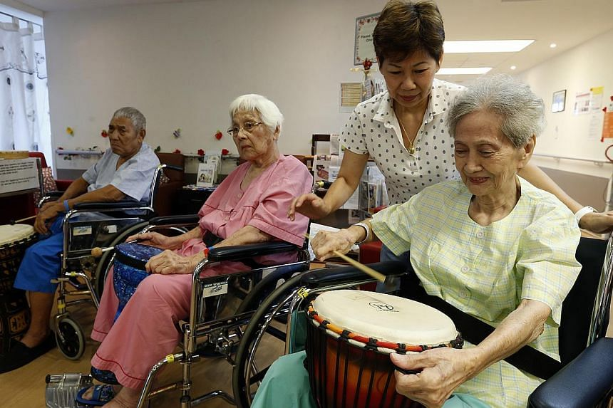 (Above, from left) Mr Taib Sany, 82, Madam Kwek Lee Khoon, 84, Madam Wendy Ow and her mother, Madam Chia Yin Peng, 88, during a music session at SACH last month. (Left) Ms Anna Lee made a patient an overcoat full of things like buttons and strings th