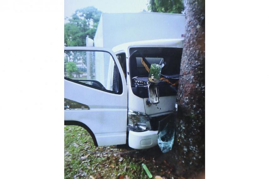 At least one man has died in an accident after a lorry slid during wet weather and hit a tree at Yishun Avenue 1 on Sunday morning. -- PHOTO: SHIN MIN
