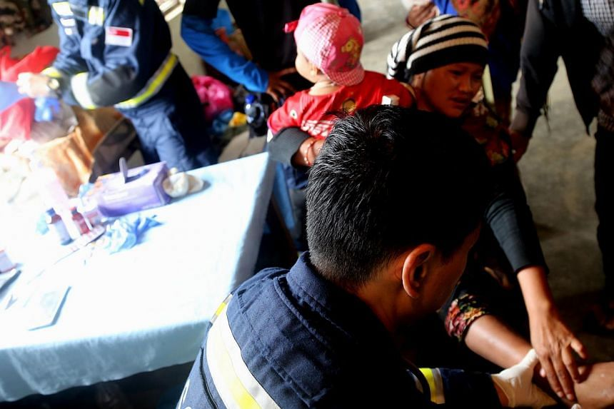 A SCDF Medical Officer examining a woman's leg. The Home Team hit its largest ever deployment for an overseas disaster relief operation with its number to Nepal totalling 126 officers. -- PHOTO: FACEBOOK OF TEO CHEE HEAN