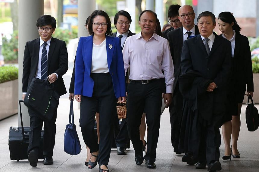 Sylvia Lim (in blue) and Muhamad Faisal Manap (centre) arriving at the High Court on May 4, 2015. The Ministry of National Development (MND) on Monday cited Aljunied-Hougang-Punggol East Town Council (AHPETC) chairman Sylvia Lim saying that the town