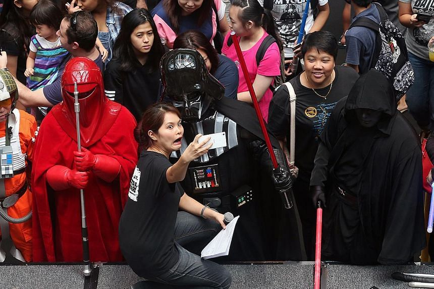 """Stage and floor emcee Ms Joanne Su (centre), 32, gets a selfie taken with Darth Vader as members of the public and fans of Star Wars attend the Star Wars Day """"Celebrate the Force"""" event held at Suntec City, east wing atrium on May 2, 2015. The two-da"""