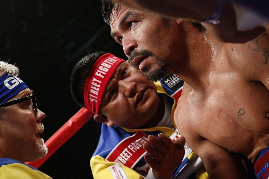 Trainer Freddie Roach (left) speaks to his fighter Manny Pacquiao of the Philippines between rounds during his welterweight unification bout against US boxer Floyd Mayweather Jr., at the MGM Grand Garden Arena in Las Vegas, Nevada on May 2, 2015. Man