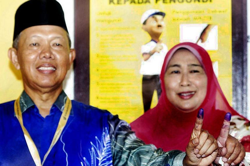 Both Datuk Hasan Arifin and wife Datin Rozidah Ab Karim showing their fingers marked with the voting ink. -- PHOTO: THE STAR