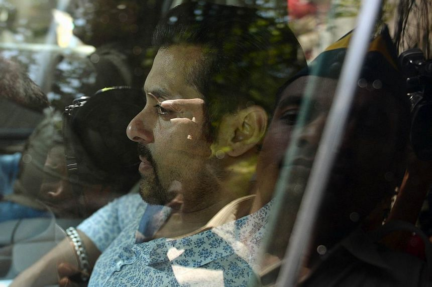 In this file photograph taken on May 6, 2014, Indian Bollywood film actor Salman Khan leaves in a car after appearing at the sessions court in Mumbai. Bollywood star Salman Khan, known for his bulging biceps and off-camera temper tantrums, faces jail