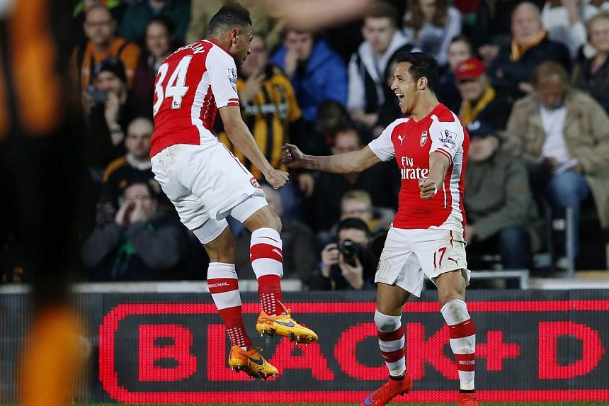 Arsenal forward Alexis Sanchez (right) celebrates with teammate Francis Coquelin after opening the scoring against Hull. -- PHOTO: REUTERS