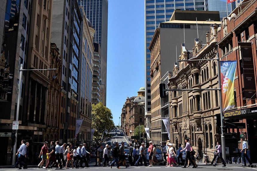 Pedestrians crossing a road in the Sydney CBD on March 3, 2015. Australia's central bank cut its cash rate a quarter point to an all-time low of 2.0 per cent on Tuesday, aiming to spur a sluggish domestic economy while keeping downward pressure on th