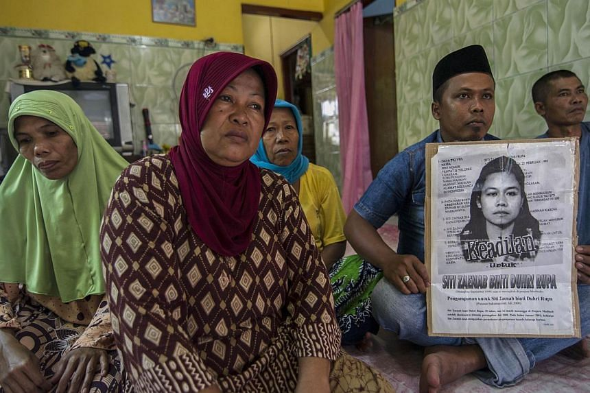 Family members of beheaded Indonesian maid Siti Zainab displaying a poster (right) bearing her portrait at their home in Bangkalan, East Java province, on April 15, 2015. Indonesia will stop sending new domestic workers to 21 Middle Eastern countries