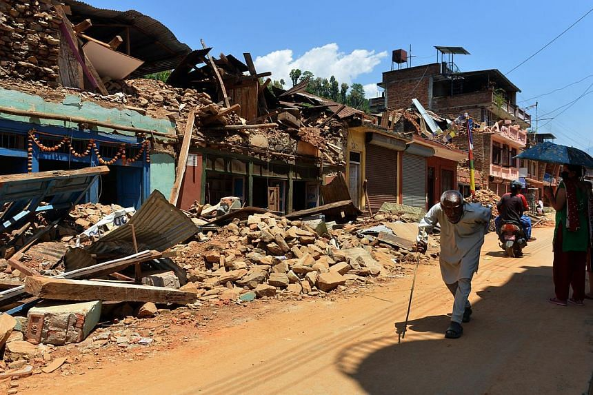 People walking past damaged houses at Trishuli in Nuwakot district north of Kathmandu on May 4, 2015. Nepali police and local volunteers found the bodies of about 100 trekkers and villagers buried in an avalanche set off by last month's devastating e