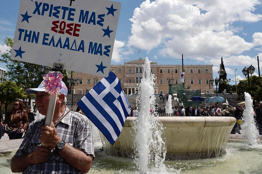 "A man holds a Greek flag and a placard reading ""Our Christ, save our Greece"" in front of the Greek parliament in Athens on April 30, 2015. -- PHOTO: AFP"