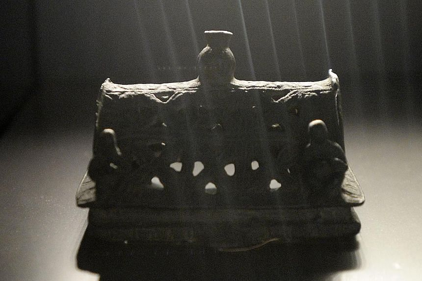 ARTEFACTS ON SHOW: A 7th century bronze miniature shrine roof (above) from Kedah in Malaysia and a gold thali or wedding pendant circa late 19th to early 20th century, most likely from Trichy, Tamil Nadu. -- ST PHOTO: MARK CHEONG