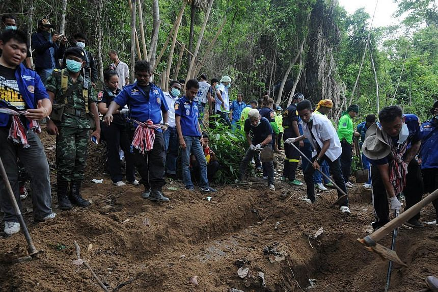 Rescue workers and forensic officials digging out skeletons from a mass grave at an abandoned jungle camp in the Sadao district of Thailand's southern Songkhla province on May 2, 2015. Investigators in southern Thailand have discovered five graves at