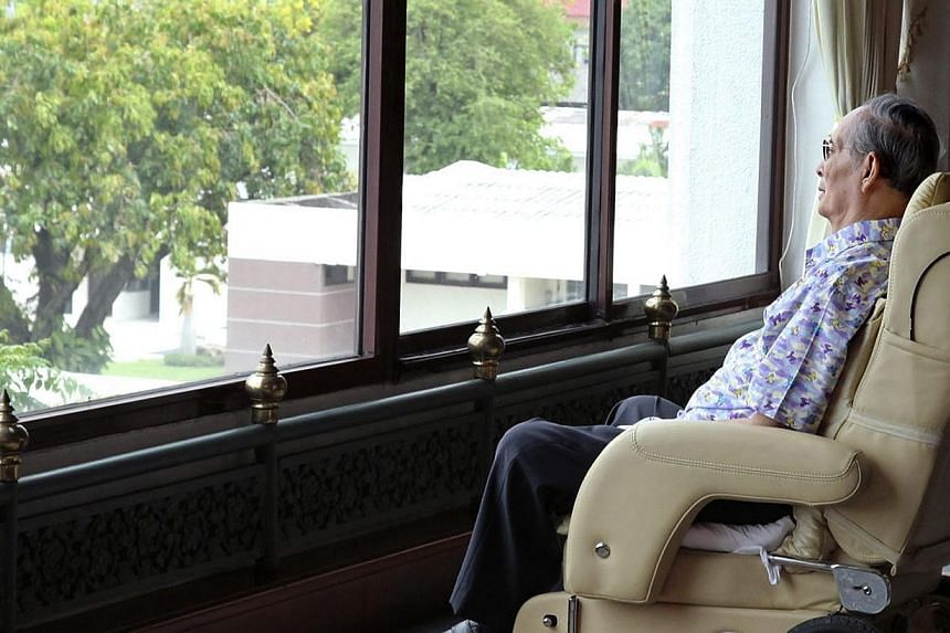 A handout photograph made available by Thailand's Royal Household Bureau on April 25, 2015, shows Thai King Bhumibol Adulyadej sitting on a wheelchair as he looks from a window at the Royal Navy Auditorium in Bangkok, Thailand, on April 23, 2015. --