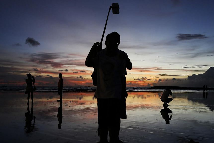 Tourists taking pictures during sunset in Kuta beach, Bali, on Feb 26, 2015. Singapore has emerged as the top contributor to tourist arrivals in Indonesia, with Bali and Bandung among the more popular destinations for Singaporeans. -- PHOTO: REUTERS&