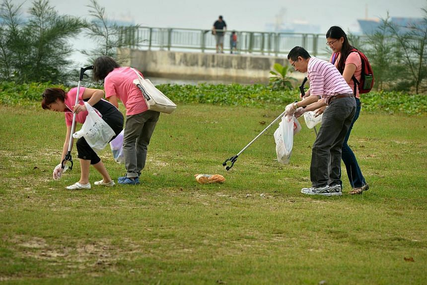 Volunteers picking up litter at East Coast Park. -- PHOTO: ST FILE