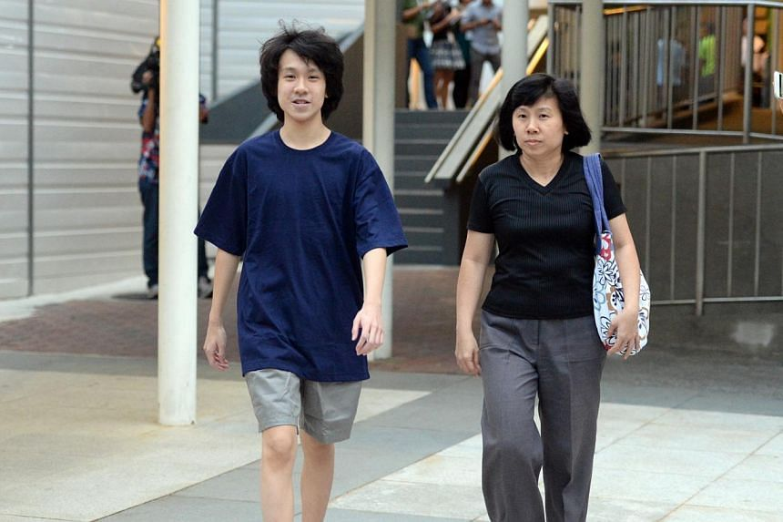 Amos Yee with his mother outside the State Courts on April 21, 2015. A bail review for the teenage blogger will be heard on Wednesday morning at the High Court. -- ST PHOTO: AZIZ HUSSIN