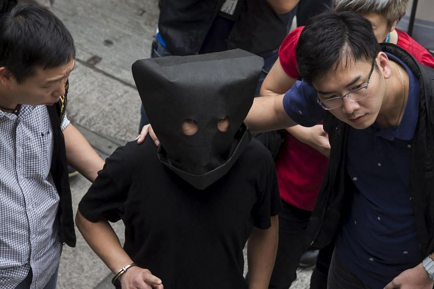 Police officers escort a man (centre, face covered), suspected to be involved in the kidnapping of a tycoon's granddaughter, as he is brought to Choi Hun MTR station for investigation in Hong Kong, China May 5, 2015. The kidnapping, an armed robbery