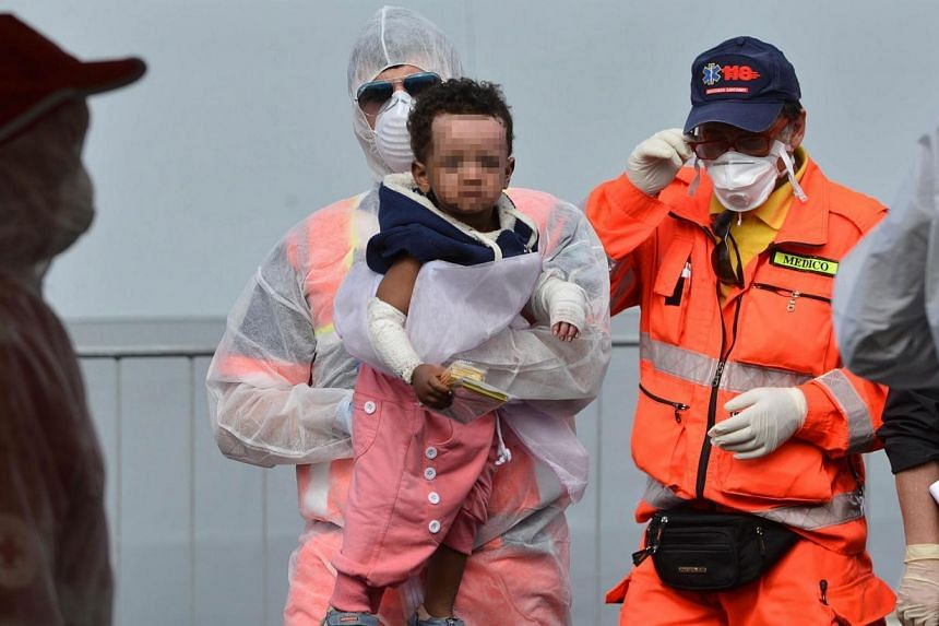 Officials assist a refugee child after they disembark from the Italian Navy vessel 'Bettica' in the harbor of Salerno, Italy, on May 5, 2015. On Monday more than 3,000 migrants landed in southern Italian ports on board the Italian navy patrol ship Be
