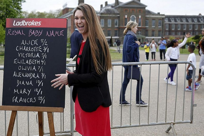 Ladbrokes spokesperson Jessica Bridge reacts outside Kensington Palace in front of a blackboard showing the odds on possible names for Britain's new baby princess after learning she was named Charlotte Elizabeth Diana, -- PHOTO: REUTERS
