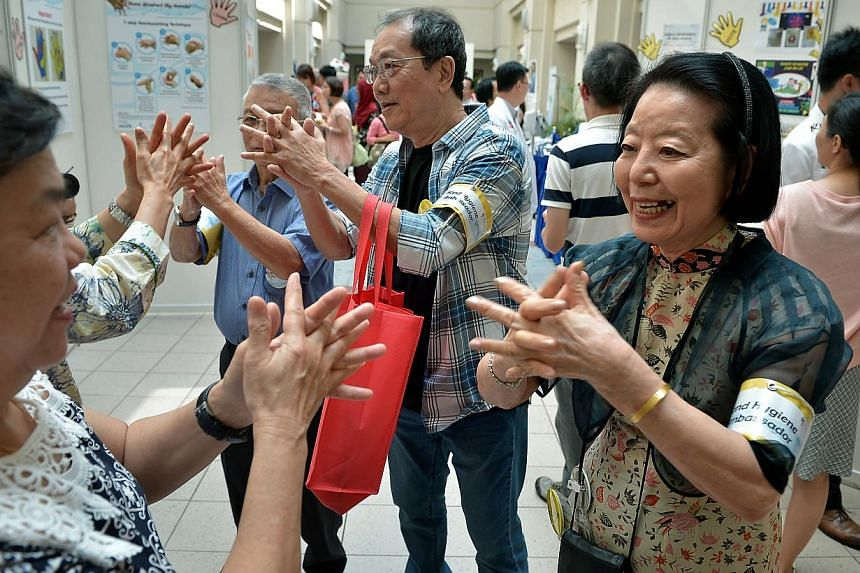 Mdm Dincy Lim, 82 (right) together with other patient leaders, Tan Yong Hua, 69 (centre) and Tan Tai Jong, 72 (left in blue) demonstrates the correct technique of cleaning ones hands. -- ST PHOTO: KUA CHEE SIONG