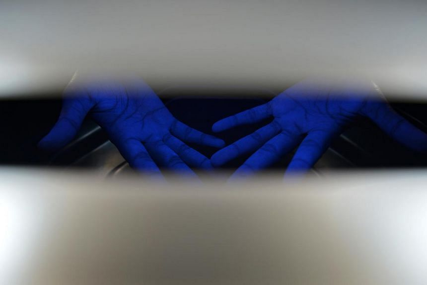 A nurse puts her hands under ultraviolet light after she had used a sanitisation gel with added phosphorescent liquid to assess whether she had sanitised her hands thoroughly.-- ST PHOTO: KUA CHEE SIONG