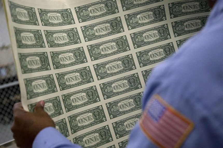 A one dollar note sheet is inspected at the US Bureau of Engraving and Printing in Washington, DC, on April 14, 2015. The Republican-led United States Congress passed a 2016 Budget on Tuesday, a largely symbolic policy document which if fully enacted