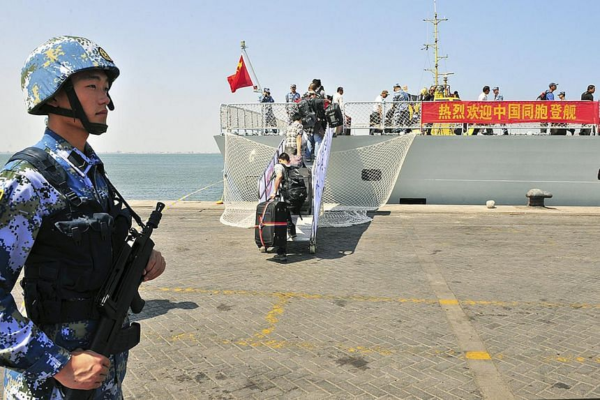 "A navy soldier (left) of People's Liberation Army (PLA) stands guard as Chinese citizens board the naval ship ""Linyi"" at a port in Aden, on March 29, 2015. -- PHOTO: REUTERS"