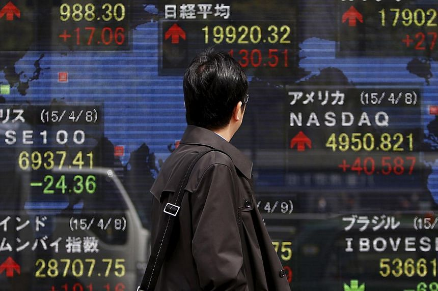 A pedestrian looking at an electronic board showing the stock market indices of various countries outside a brokerage in Tokyo on April 9, 2015. Asian stocks stumbled on Wednesday in sympathy with weak US and European markets as equities investors we