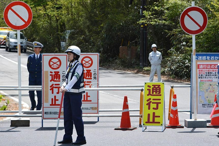 Police and other officials standing at a roadblock halting access to a popular hot springs resort in Hakone, Kanagawa prefecture on May 6, 2015. -- PHOTO: AFP