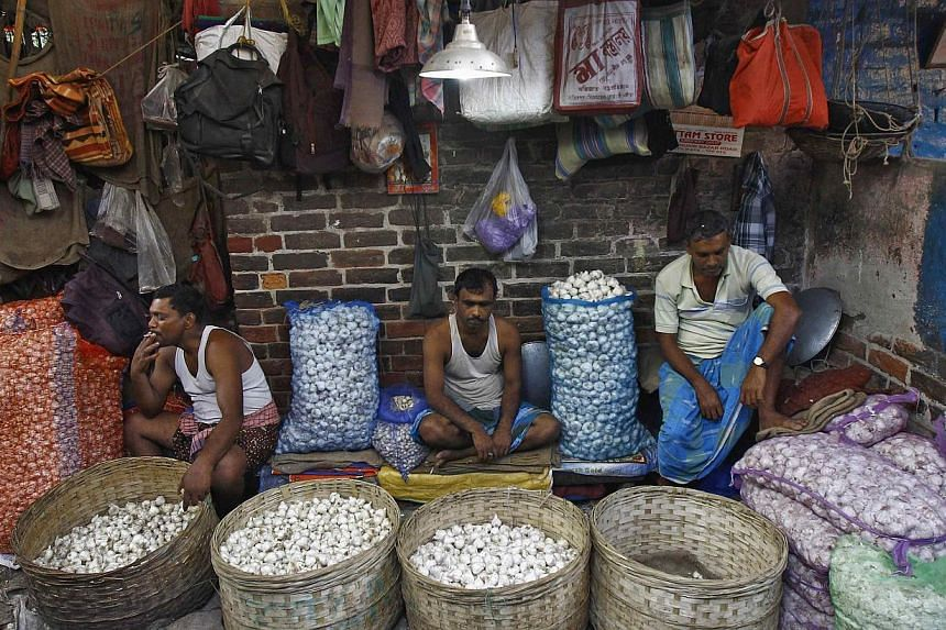Garlic vendors waiting for customers at their stall at a wholesale vegetable market in Kolkata on Feb 27, 2015. India's lower house of parliament passed a bill on Wednesday, May 6, that seeks to transform the country into a common market with a singl