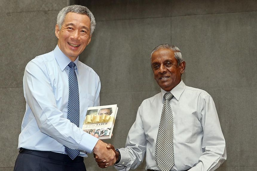 Former Senior Minister S Jayakumar (right) presenting Prime Minister Lee Hsien Loong with a copy of his book, Be At The Table Or Be On The Menu: A Singapore Memoir, at its launch at the Ministry of Foreign Affairs on Wednesday, May 6, 2015. -- ST PHO