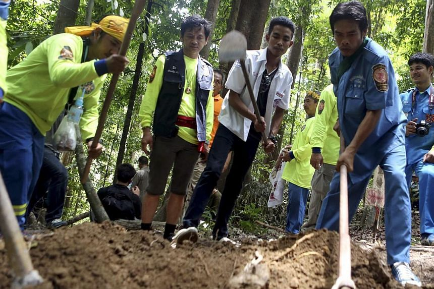 Thai rescue workers dig to recover human remains of suspected Rohingya refugees after discovering a second abandoned migrant trafficking camp at a jungle on a mountain in the Sadao district, Songkhla province, near the Thai-Malaysian border in southe