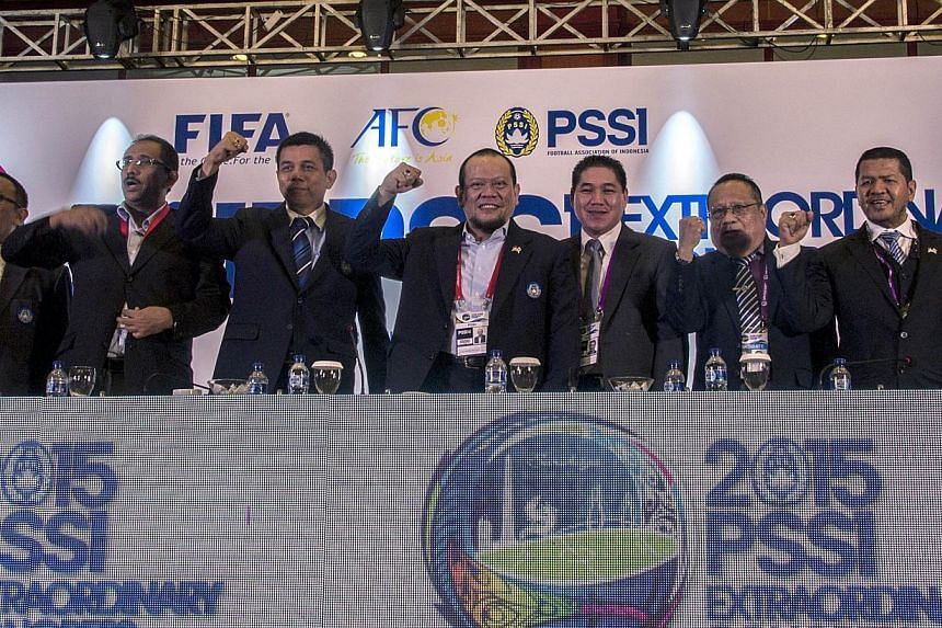 This photo taken on April 18, 2015 shows newly-elected Indonesian Football Association (PSSI) chief La Nyalla Mattalitti (fourth left) standing with new officials of the PSSI following his election in Surabaya, East Java province. FIFA has ordered th