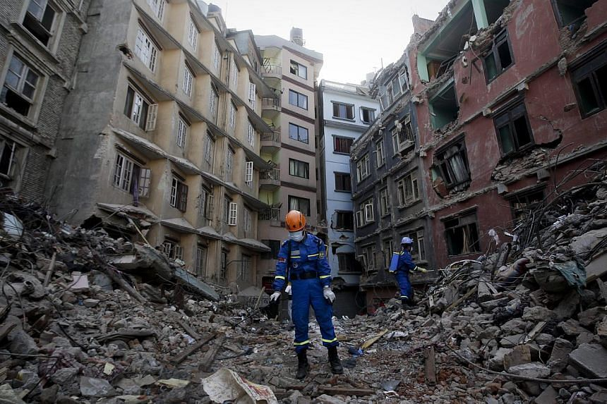 Members of a Chinese recovery team disinfect debris from destroyed buildings in Balaju, Kathmandu, after the devastating earthquake that hit the country on April 25, 2015. -- PHOTO: EPA
