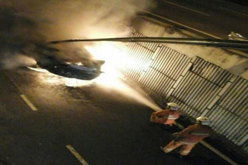 Firefighters putting out the flames from the Maserati Quattroporte, which had crashed into a side railing on an elevated portion of the Sprint Highway. -- PHOTO: THE STAR/ASIA NEWS NETWORK