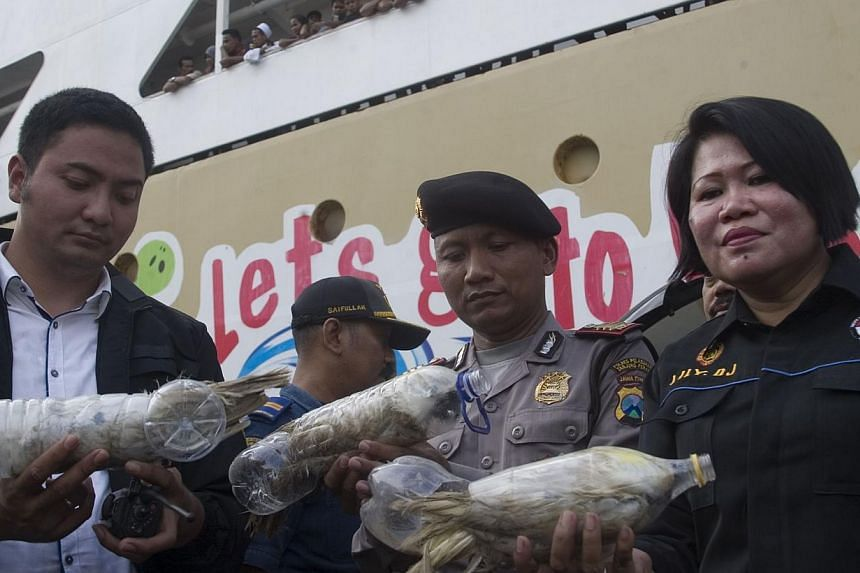 Indonesian police and customs officials hold rare Indonesian yellow-crested cockatoos placed inside water bottles confiscated from alleged wildlife smuggler. -- PHOTO: REUTERS