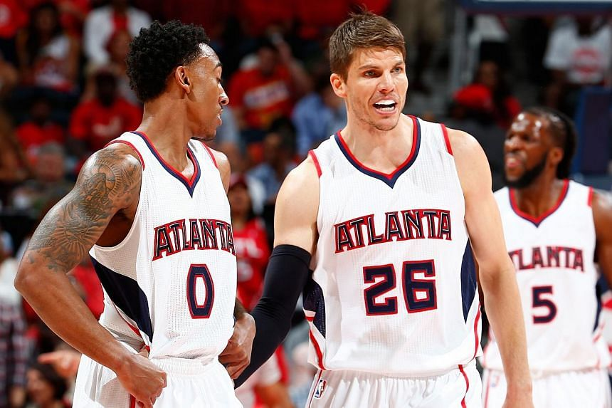 Kyle Korver (centre) of the Atlanta Hawks converses with Jeff Teague (left) during Game Two of the Eastern Conference Semifinals against the Washington Wizards at the Philips Arena, Atlanta, Georgia, on May 5, 2015. -- PHOTO: AFP