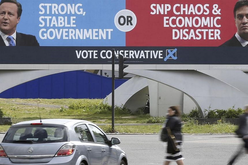 People walk under a conservative advertising hoarding, featuring David Cameron and Labour party leader, Ed Miliband, on a major road junction near to central London, Britain on May 6, 2015.Campaigning in Britain's most unpredictable election in