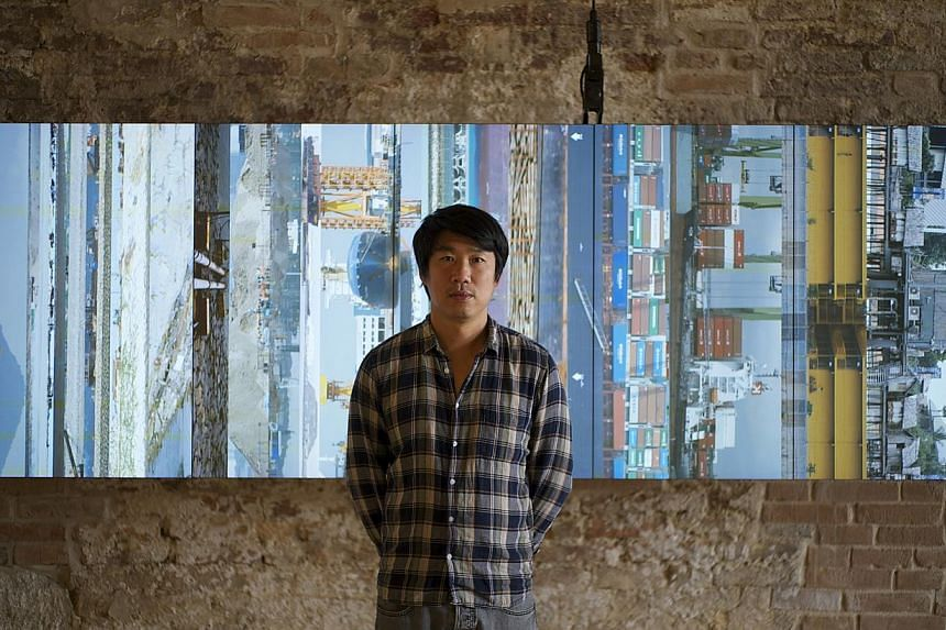 Artist Charles Lim and his installation Sea State at the Singapore Pavilion. Sea State looks at the impact of reclamation and expansion works in Singapore and includes maps, charts, video installations and a 5-m tall aluminium buoy encrusted with bar