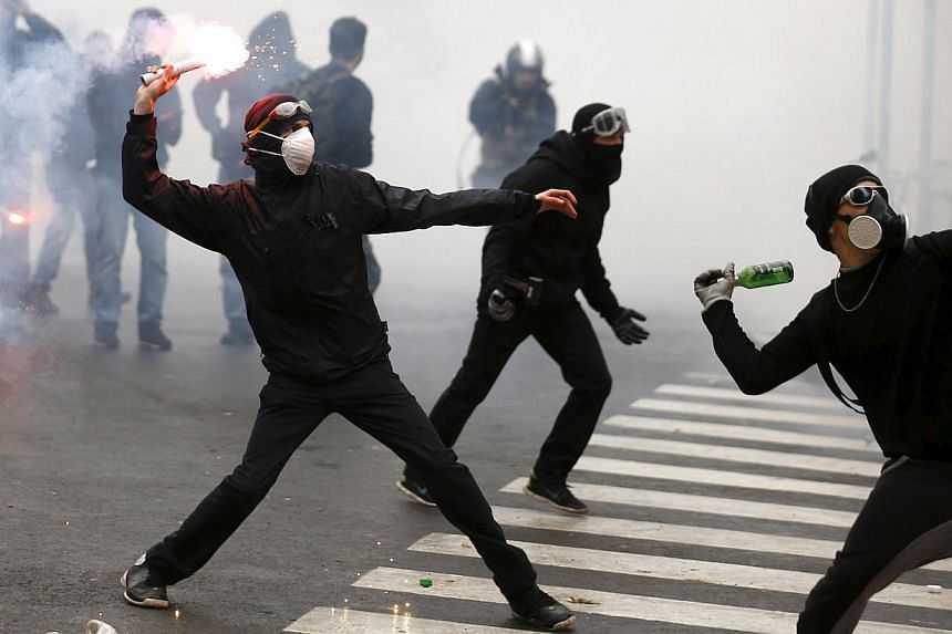 Protesters throwing bottles and flares during a rally against Expo 2015 in Milan, Italy, on May 1, 2015. Swiss watchmaker Rolex demanded an apology from the Italian government saying that the latter had damaged the former's reputation by portraying t