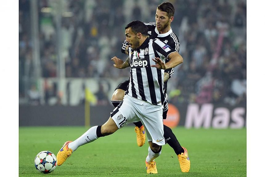 Juventus' forward Carlos Tevez (left) fights for the ball with Real Madrid's defender Sergio Ramos (right) during the UEFA Champions League semi-final first leg football match Juventus vs Real Madrid on May 5, 2015 at the Juventus stadium in Turin. -
