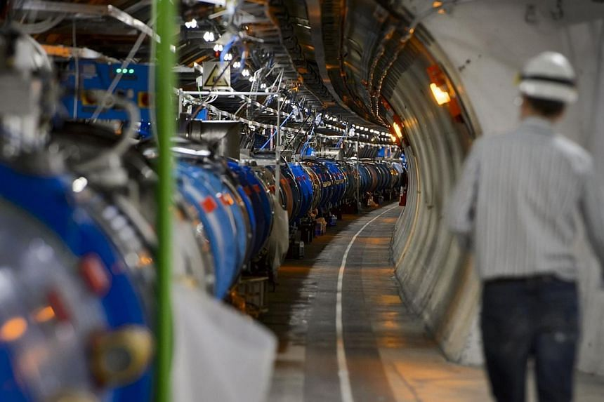 A scientist walks in a tunnel inside the European Organisation for Nuclear Research (CERN) Large Hadron Collider (LHC), during maintenance works on July 19, 2013 in Meyrin, near Geneva. -- PHOTO: AFP