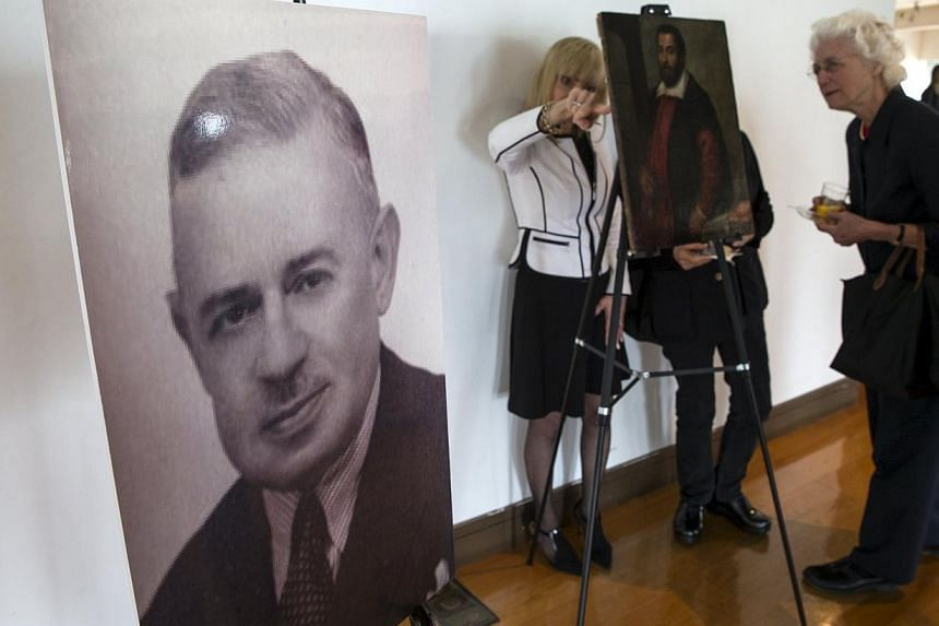 A photograph of German Holocaust victim Dr. August Liebmann Mayer, stands next to the 17th century painting Portrait of a Man which belonged to Dr Mayer at a ceremony at the Jewish Heritage Museum in New York officially returning the painting to Maye