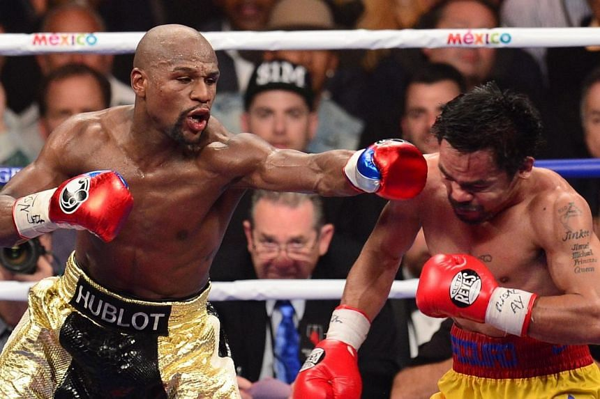 Floyd Mayweather Jr. (left) connects against Manny Pacquiao (right) during their welterweight unification bout on Saturday at the MGM Grand Garden Arena in Las Vegas. Mayweather remains undefeated with a unanimous decision. -- PHOTO: AFP