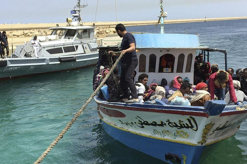 Illegal migrants who attempted to sail to Europe sit in a boat returning them to Libya as it is docked, after their boat was intercepted at sea by the Libyan coast guard, at Khoms, Libya. -- PHOTO: REUTERS