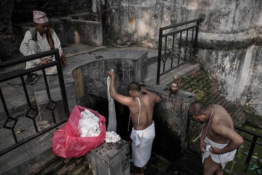 Nepalese Hindu devotees take part in a mourning ritual at the Pashupatinath temple in Kathmandu on May 7, 2015. Dressed all in white and with their heads shaved, survivors of a Nepalese earthquake that killed more than 7,800 people ended 13 days of m