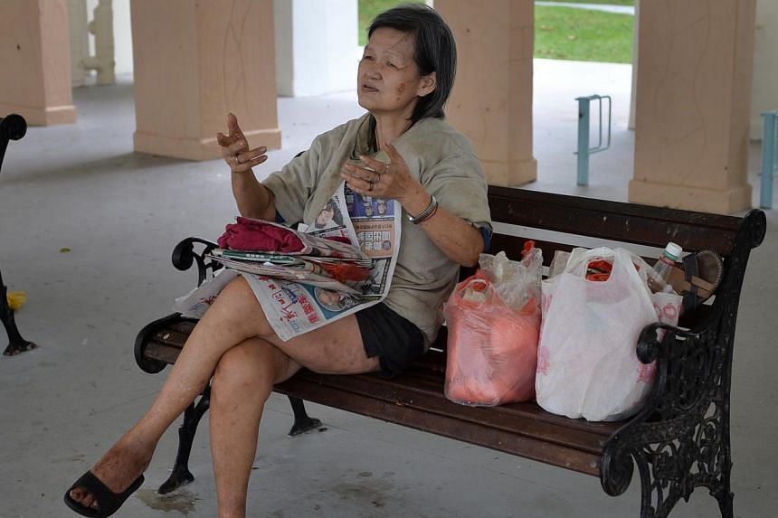 Madam Soh Siew Zhen,a hoarder, sitting on a void deck bench with two plastic bags of leftover food and drinks. -- PHOTO: THE NEW PAPER