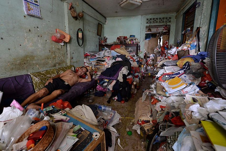 Mr Lim Chin Ting has to sleep on the sofa in the living room because both bedrooms are filled to the brim with rubbish. Mr Lim, a drinks assistant at a coffee shop nearby, has to live in a three-room flat that is filled with junk at Block 19 Eunos Cr