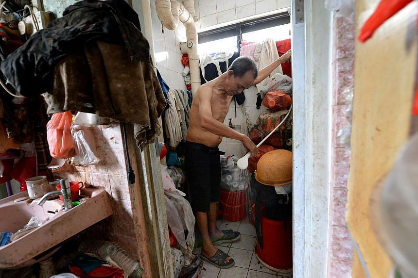 Mr Lim Chin Ting demonstrating how he showers every day in a toilet that is filled with junk. Mr Lim, a drinks assistant at a coffee shop nearby, has to live in a three-room flat that is filled with junk at Block 19 Eunos Crescent because his wife, M